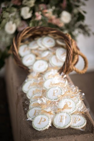 wedding-favors-in-wicker-basket-wrapped-cookie-with-laurel-wreath-design-and-initial-monogram