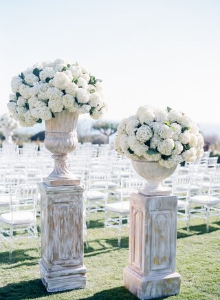 seaside-wedding-ceremony-with-clear-chiavari-chairs-and-urns-filled-with-white-hydrangeas-on-stands