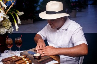man-in-white-shirt-with-cuban-hat-rolling-tobacco-leaves-for-cigar-station-at-wedding