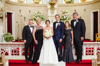 bride-in-legends-romona-keveza-wedding-dress-groom-in-navy-suit-with-parents-at-church-altar