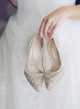 bride-with-oval-cut-diamond-engagement-ring-holding-oscar-de-la-renta-wedding-pumps