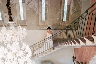 bride-in-illusion-wedding-dress-walking-up-stairs-of-chateau-venue-in-the-south-of-france
