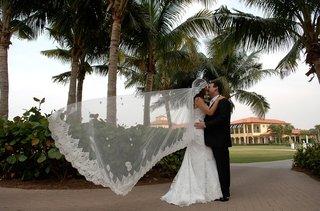 bridal-veil-blowing-in-wind-while-bride-kisses-groom