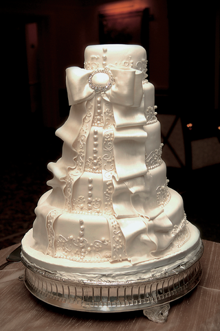 white-wedding-cake-with-buttons-lace-and-bow