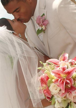 couple-kissing-holding-pink-and-green-flowers