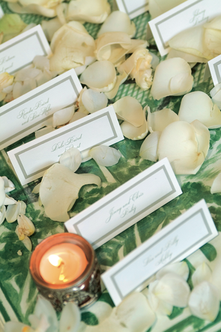 wedding-reception-place-cards-on-a-green-print-tablecloth-surrounded-by-petals
