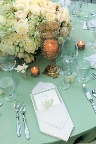 reception-dinner-table-with-a-light-green-table-cloth-white-and-light-green-flowers-and-candles
