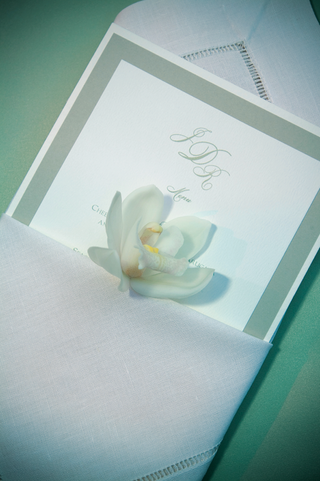 wedding-reception-dinner-menu-with-a-light-green-border-in-a-white-cloth-napkin-with-an-orchid