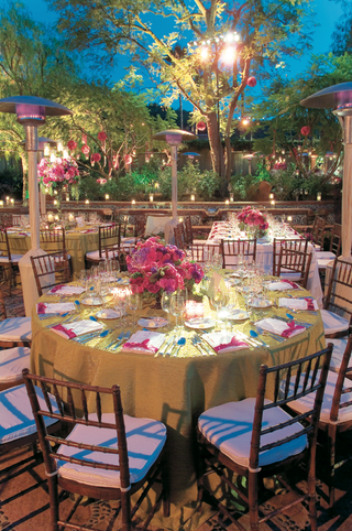green-reception-table-under-trees-with-pink-centerpiece