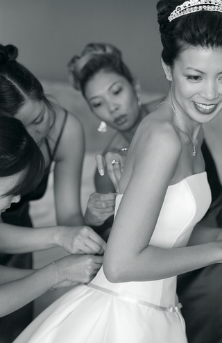 black-and-white-image-of-bridesmaids-help-the-bride-button-her-wedding-dress