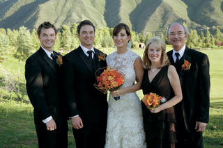 bride-in-a-lace-monique-lhuillier-gown-and-groom-in-a-black-tuxedo-with-family