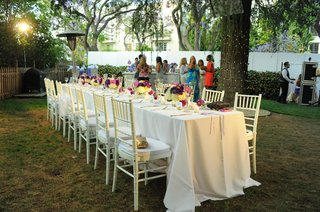 long-white-table-with-purple-and-pink-centerpieces
