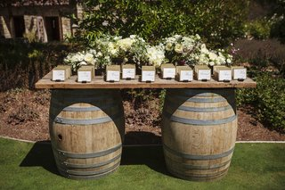 ranch-wedding-reception-with-place-card-table-composed-of-two-barrels-and-wood-board-white-flowers