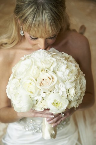 bride-with-bangs-smelling-ivory-flowers