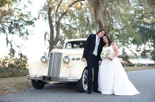 bride-and-groom-standing-in-front-of-classic-pale-yellow-car