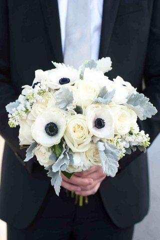 groom-holding-dusty-miller-with-ivory-rose-and-white-and-blue-anemone-bouquet