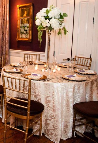 gold-plates-and-chairs-with-white-flower-centerpiece-and-taupe-tablecloth