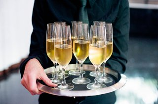 wedding-reception-cocktail-hour-server-in-black-shirt-and-tie-holding-tray-silver-rim-champagne