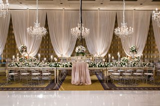 wedding-reception-decor-drapery-chandelier-long-head-table-mirror-clear-chairs-high-low-centerpieces