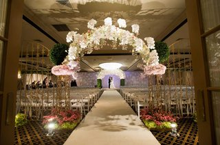 wedding-ceremony-with-a-bronze-gate-decorated-with-white-orchids-roses-and-pink-roses