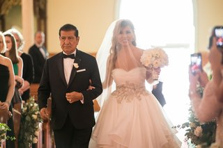 bride-in-alyne-ball-gown-with-large-belt-blusher-veil-walks-down-aisle-with-father-in-tux