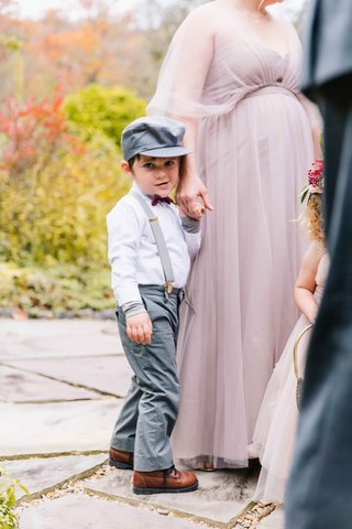 little-boy-in-gray-pants-and-suspenders-and-hat-with-purple-bow-tie-and-brown-shoes