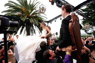 guests-lift-bride-and-groom-in-chairs-for-jewish-tradition