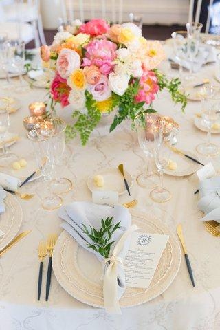 wedding-reception-table-beige-linen-blue-napkin-flatware-pink-yellow-orange-flower-centerpiece