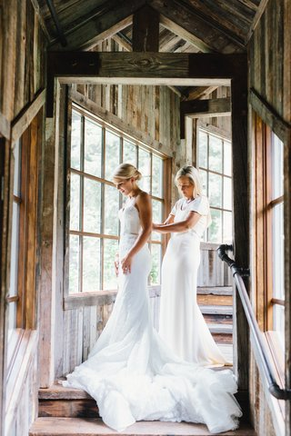 the-mother-of-the-bride-in-white-short-sleeve-dress-helping-bride-into-inbal-dror-gown