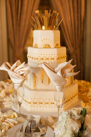 white-wedding-cake-with-hexagon-shaped-tiers-and-gold-embellishments