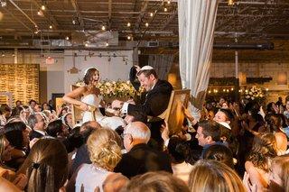 couple-in-hora-chair-dance-jewish-wedding