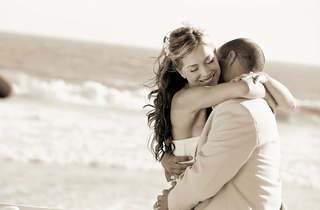 bride-and-groom-hug-on-beach-near-ocean