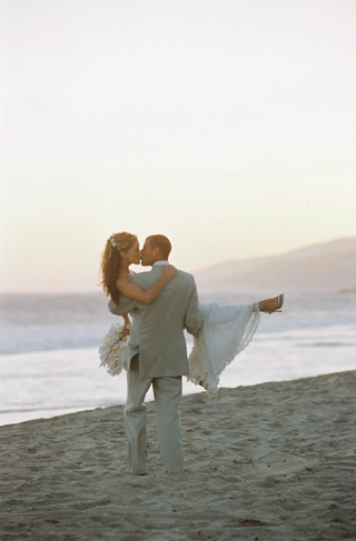 groom-picks-up-bride-on-beach-and-walks-towards-ocean