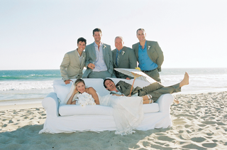 bride-and-groom-with-family-on-white-sofa-on-beach