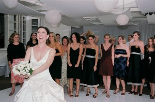 bride-prepares-to-toss-bouquet-to-bridesmaids-and-guests