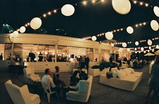 white-couches-and-lanterns-adorn-a-nighttime-outdoor-reception