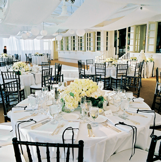 white-tablecloths-and-flower-arrangements-with-black-chairs