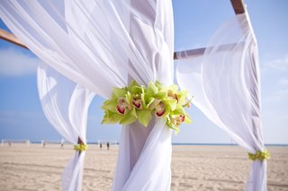 white-drapery-on-beach-ceremony-altar-with-orchids