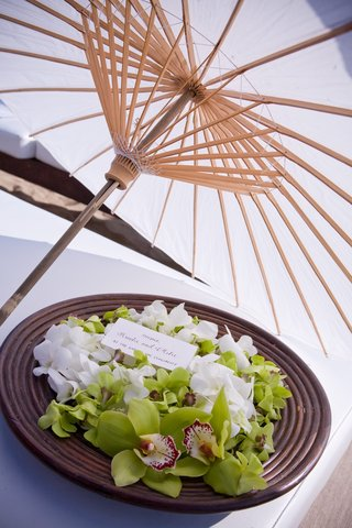 plate-of-green-orchids-under-parasol-at-beach-wedding