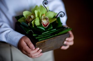 wood-box-with-jungle-leaves-and-green-orchids