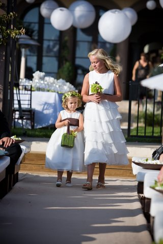 two-flower-girls-walk-down-beach-wedding-aisle