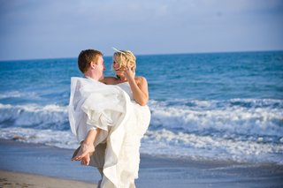 wedding-photo-of-groom-picking-up-bride-on-beach