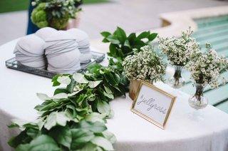 grey-yarmulke-table-with-wedding-hashtag-sign-babys-breath-green-garland-on-table