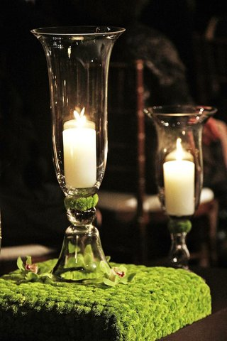 candle-in-glass-vase-on-top-of-green-flower-stand