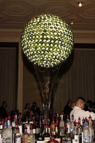 globe-of-green-limes-and-white-flowers-on-glass-vase