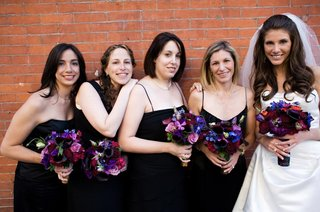 bridesmaids-wearing-black-spaghetti-strap-dresses-and-holding-purple-and-pink-bouquets