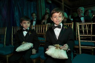 two-ring-bearers-wearing-tuxedos-hold-pillows