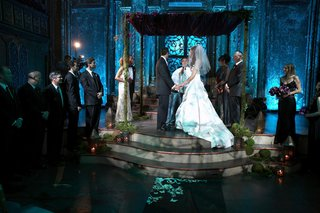 chuppah-of-greenery-stands-on-raised-platform-lit-with-blue-uplighting