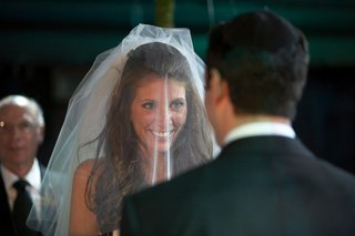 bride-faces-groom-during-ceremony-wearing-veil