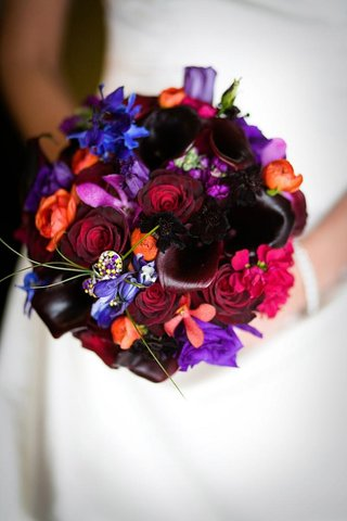 bouquet-with-red-blue-purple-pink-and-orange-flowers-and-jeweled-pin